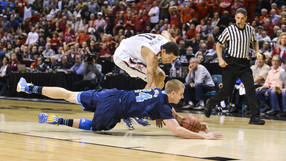 """<p>UCLA redshirt senior David Wear <a href=""""http://pac-12.com/article/2014/03/15/2014-pac-12-tournament-bracket-update-uclas-travis-wear-dives-loose-ball"""" target=""""_blank"""">hitthe deck to snatch up a loose ball</a> ahead of Arizona's Aaron Gordon in the 2014 Pac-12 Men's Basketball Tournament championship game March 15 in Las Vegas. The Bruins needed every possession as they knocked off the Wildcats 75-71.</p>"""