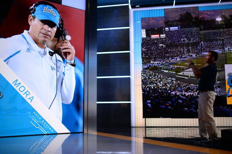 UCLA head coach Jim Mora stops to take a picture of his floor-to-ceiling graphic on the set of SportsCenter in Bristol, CT.