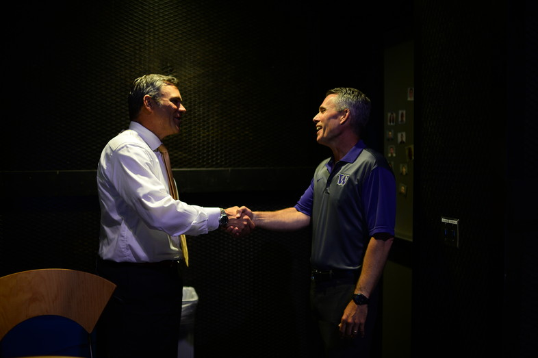 Washington's Chris Petersen shakes hands with former Washington quarterback Mark Brunell at ESPN in Bristol, CT