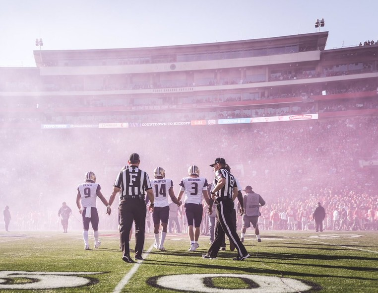 Washington captains lock hands as the smoke settles on the field.