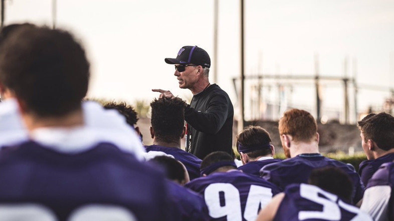 The Huskies huddle around head coach Chris Petersen following a practice in Southern California.
