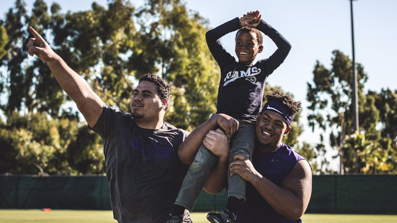 Washington linemen carry a young participant during a YMCA event following practice.