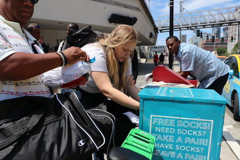 As part of Tuesday's Day of Service with HanesBrands, volunteers add socks to a box for those who need them in downtown Seattle.