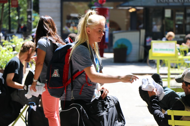 Arizona women's tennis student-athlete Sophia Thomas distributes socks to the homeless in downtown Seattle as part of Tuesday's Hanes Day of Service.