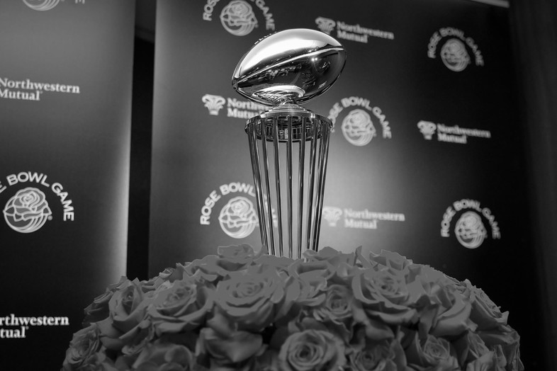 The Rose Bowl trophy stands tall around a bouquet of roses.